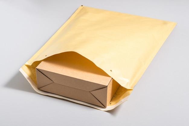 大きな郵便封筒の中の茶色の段ボール箱 Premium写真