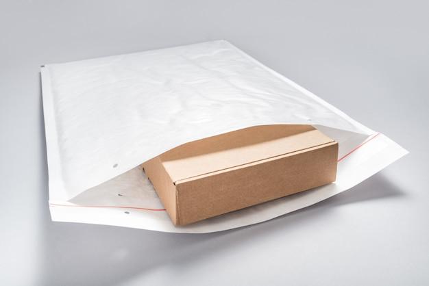 灰色の背景に白いバブルの封筒に詰められた茶色の段ボール箱 Premium写真