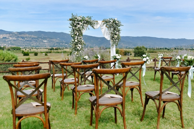 Brown chiavari chairs and the decorated wedding archway with white flowers and greenery on the sunny day Free Photo