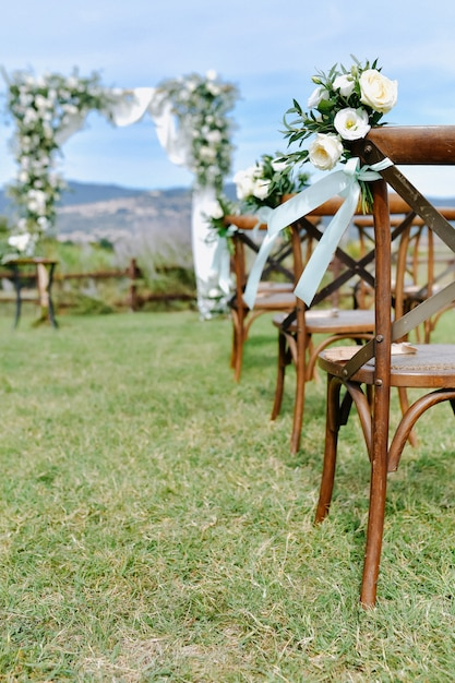 Brown chiavari chairs decorated with white eustomas on the grass and the decorated wedding archway on the background Free Photo
