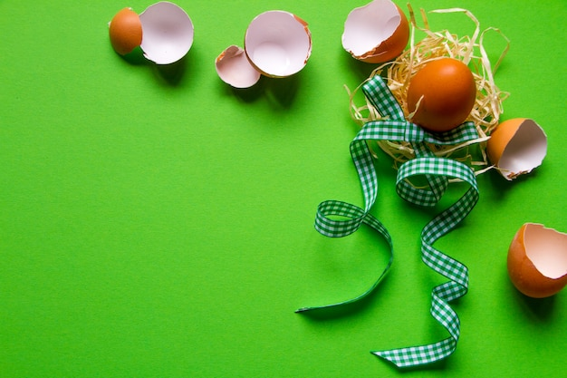 Brown chicken egg in a straw nest, broken eggshell and green checkered ribbon Premium Photo