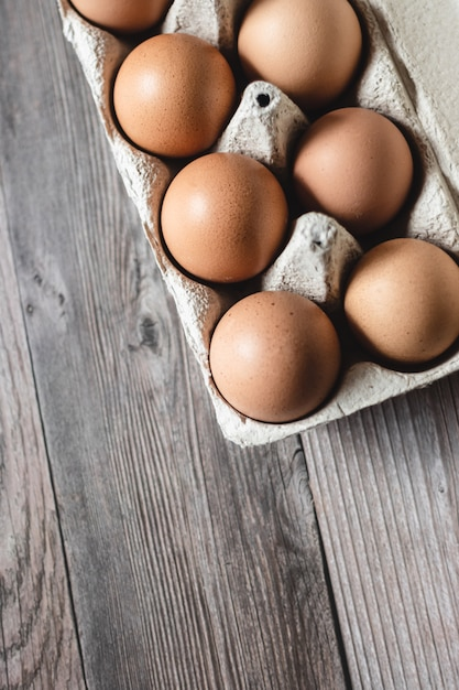 Brown chicken eggs in a carton on wooden surface. top view. Premium Photo