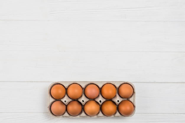 Brown chicken eggs in rack on white table Free Photo