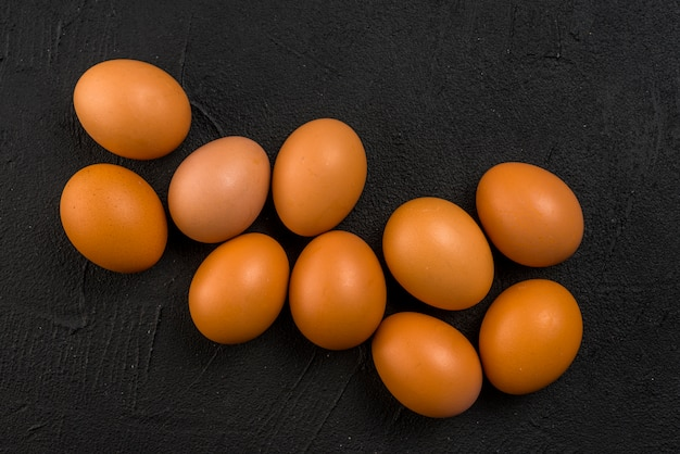 Brown chicken eggs scattered on black table Free Photo