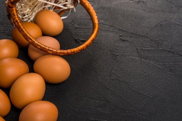 Brown chicken eggs with basket on table Free Photo