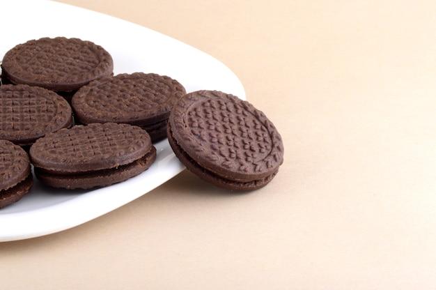 ブラウンチョコレートサンドイッチビスケット、プレートにクリームを充填 Premium写真