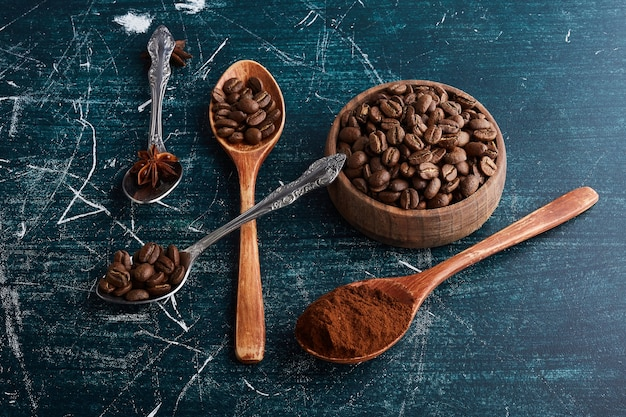 Brown coffee beans in wooden cup and spoons. Free Photo