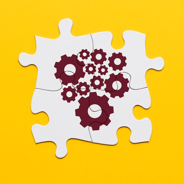 Brown cogwheel on white connected puzzle on yellow surface Free Photo