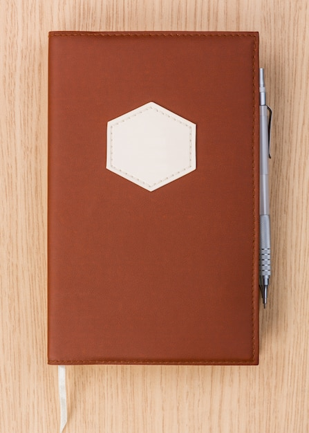Brown diary with pen Free Photo