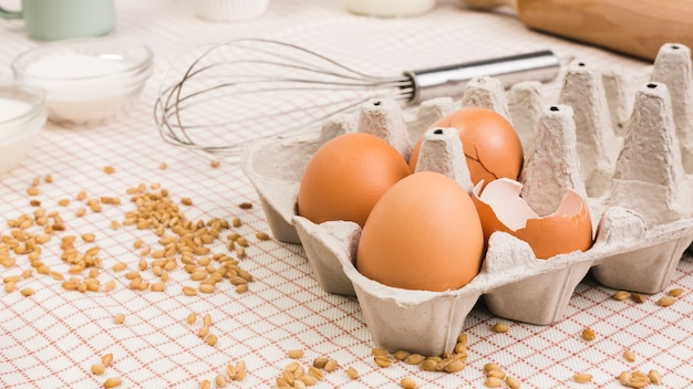 Brown eggs in carton near wheat grain and whisk over table cloth Free Photo