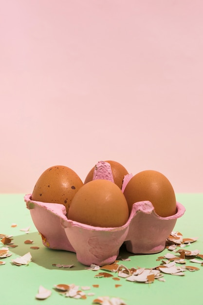 Brown eggs in rack with broken shell on green table Free Photo