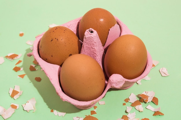Brown eggs in rack with broken shell on table Free Photo