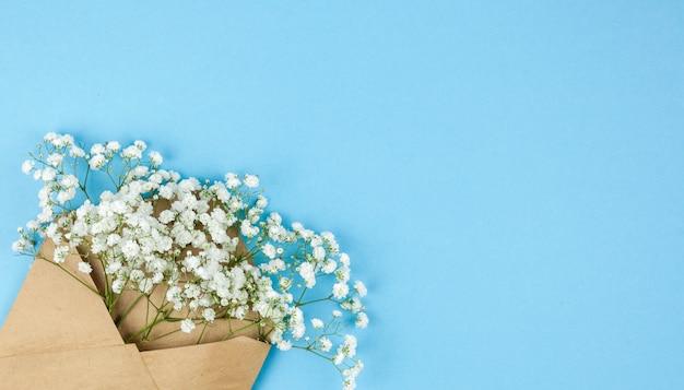 파란색 배경의 모서리에 배열 된 작은 흰색 라든지 꽃과 갈색 봉투 무료 사진
