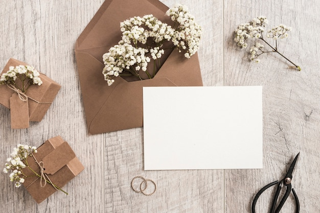 Brown envelope with baby's-breath flowers; gift boxes; wedding rings; scissor and white card on wooden background Free Photo