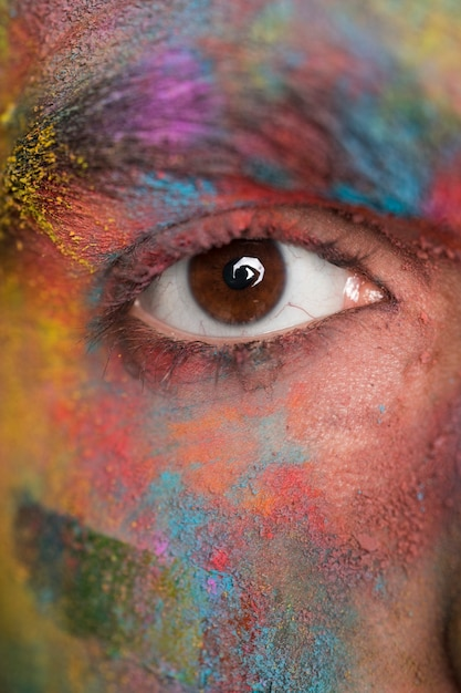 Brown eye of young man with bright colorful paint Free Photo