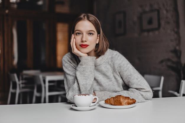 ウールのセーターを着た茶色の目の少女は、カフェの白いテーブルに寄りかかってカメラを見ていました。コーヒーとクロワッサンを注文する赤い唇を持つ女性の写真。 無料写真