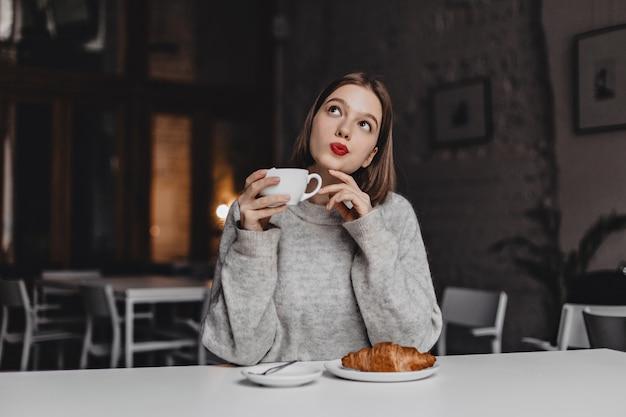 お茶と思慮深くポーズをとる赤い口紅の茶色の目の女性。クロワッサンとテーブルに座っている灰色のセーターの女性。 無料写真