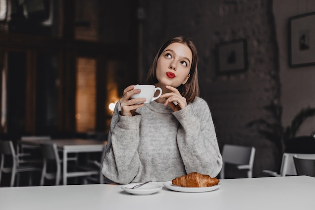 Brown-eyed lady with red lipstick posing thoughtfully with cup of tea. woman in gray sweater sitting at table with croissant. Free Photo