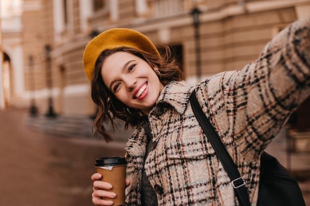 オレンジ色のベレー帽の茶色の目の女性は、美しい家の壁に対して自分撮りをします 無料写真
