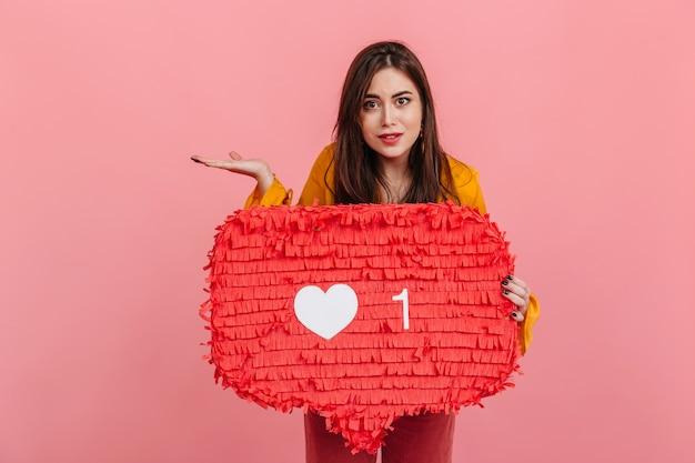 Кареглазая женщина недоуменно смотрит, держа в руках знак «нравится» из социальных сетей. Бесплатные Фотографии