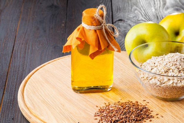 木のテーブルにガラスの水差しのspoonnd亜麻仁油に茶色の亜麻の種子。アマニ油はオメガ3脂肪酸が豊富です。 Premium写真