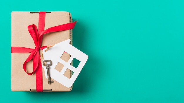 Brown gift box tied with red ribbon; and house key over turquoise surface Free Photo
