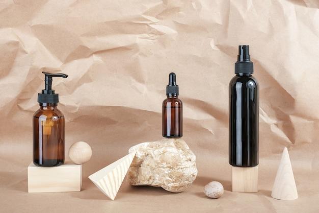 Коричневые стеклянные бутылки косметической продукции на камне Premium Фотографии