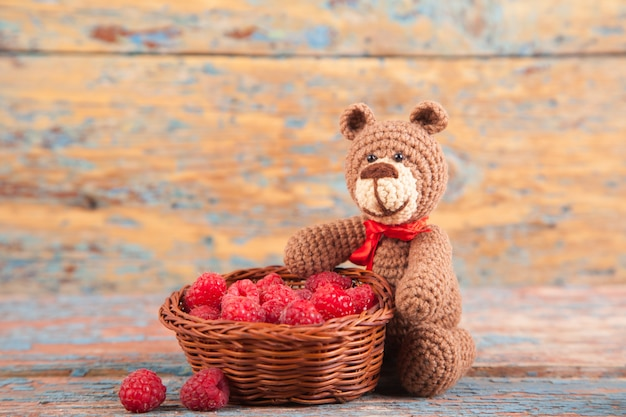 Brown knitted small bear with berry on an old wooden background. handmade, knitted toy. amigurumi Premium Photo