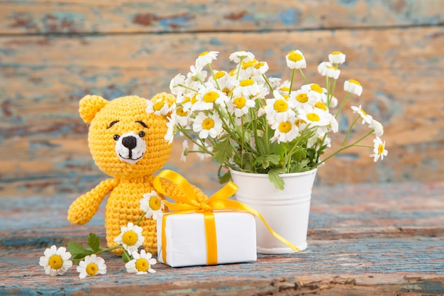 Brown knitted small bear with chamomile on an old wooden background. handmade, knitted toy. amigurumi Premium Photo