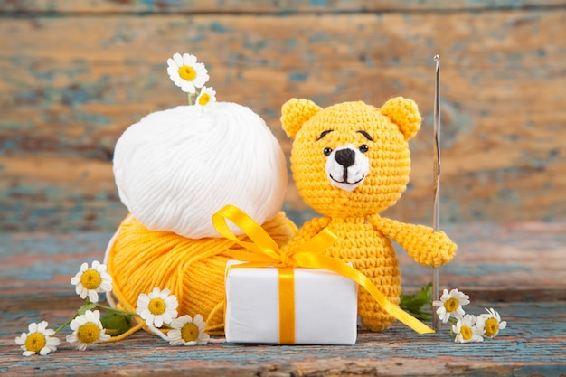 Brown knitted small bear with chamomile on an old wooden . handmade, knitted toy. amigurumi Premium Photo