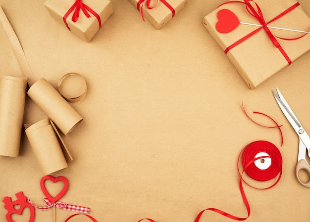 Brown kraft paper, packed gift bags and tied with a red ribbon Premium Photo