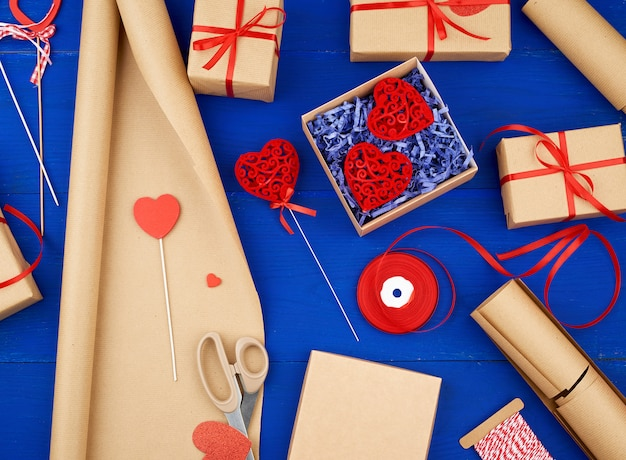Brown kraft paper, packed gift boxes and tied with a red ribbon, red heart, set of items for making gifts Premium Photo