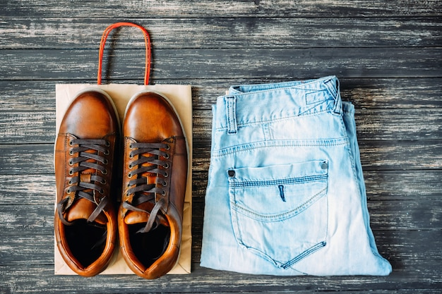 Brown leather men's boots and jeans on a wooden background, top view Premium Photo