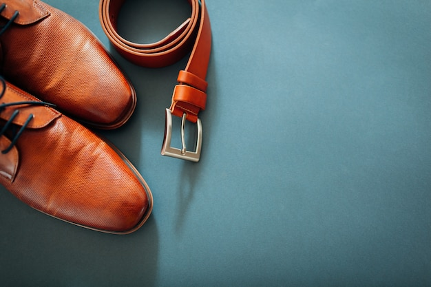 Brown leather shoes, belt, perfume and golden rings. Premium Photo