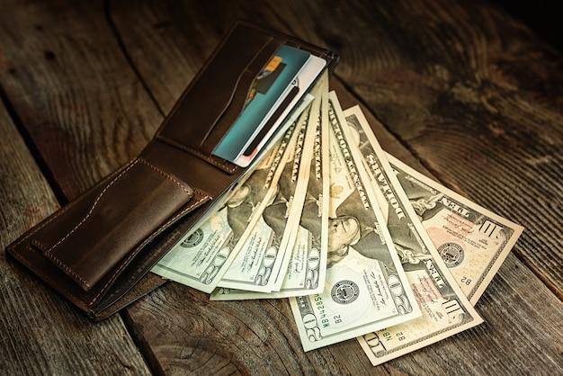 Коричневый кожаный бумажник с долларами на старой деревянной поверхности. закройте вверх. Premium Фотографии