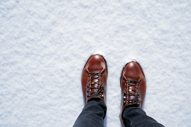 Brown men's hiking shoes on snow in sunny winter day. Premium Photo