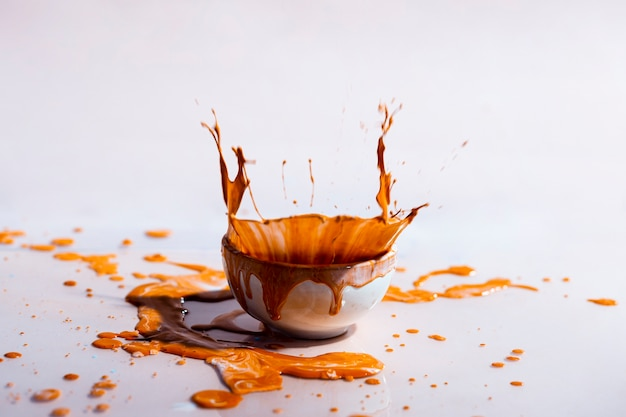Brown paint splash and cup abstract background Free Photo
