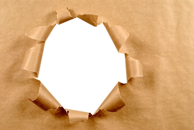Brown paper background with torn hole Free Photo