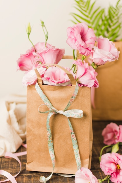 Brown paper bag with fresh pink eustoma flower on wooden table Free Photo