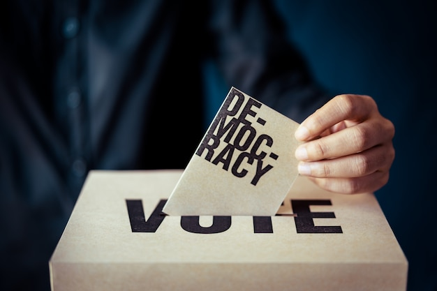 Brown paper insert in vote box, democracy concept, retro tone Premium Photo