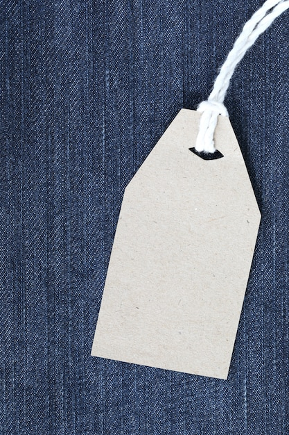 Brown paper label with hemp rope tied on denim or jeans. Premium Photo
