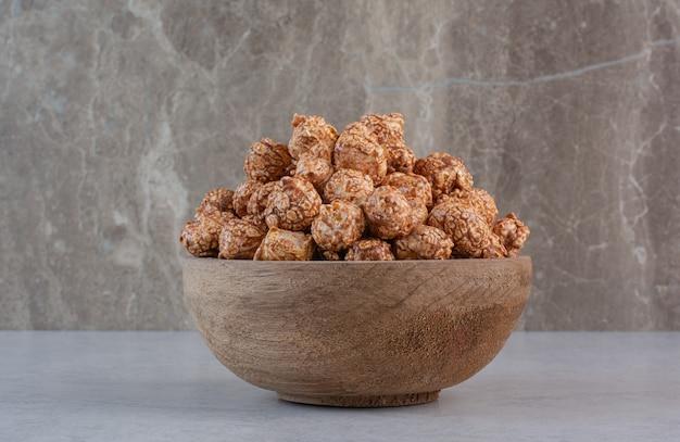 Caramelle di popcorn marrone ammucchiate in una piccola ciotola su marmo. Foto Gratuite