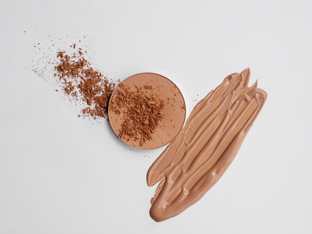 Brown powder and foundation with white background Free Photo