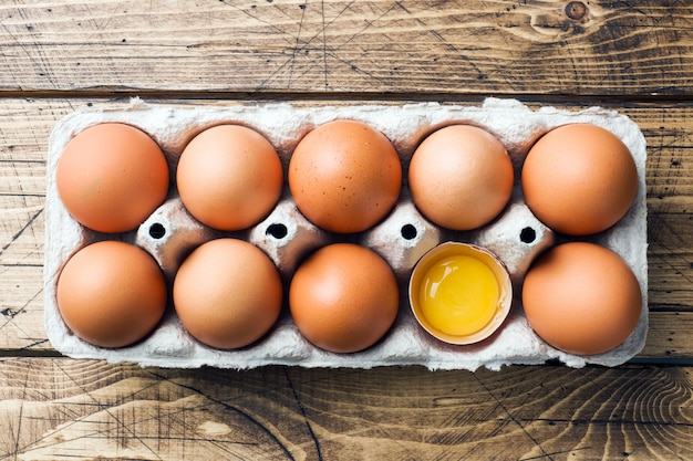 Brown raw eggs in factory packaging on rustic wooden background. Premium Photo