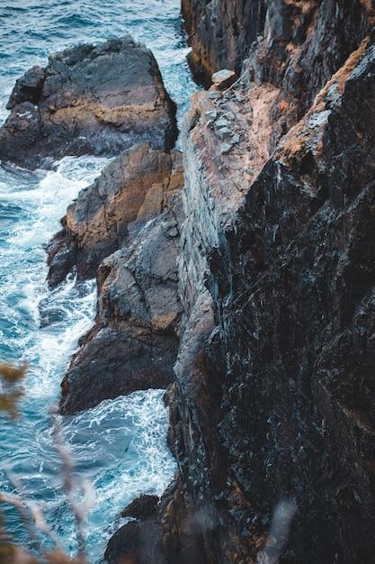 Коричневая скалистая гора у водоема днем Бесплатные Фотографии