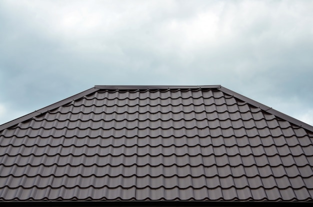 Brown roof tiles or shingles on house as background image. new overlapping brown classic style roofing material texture pattern on a actual house Premium Photo