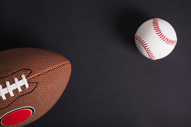 Brown rugby ball and baseball on black background Free Photo