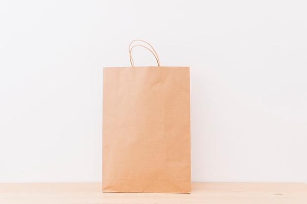 Коричневый хозяйственный мешок на деревянной поверхности Бесплатные Фотографии