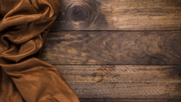 Brown silk textile on weathered wooden table Premium Photo