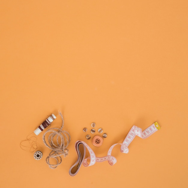 Brown spool; string; buttons and measuring tape on an orange backdrop Free Photo